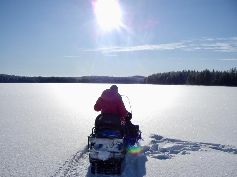 Sneeuwscooteren op een bevroren meer
